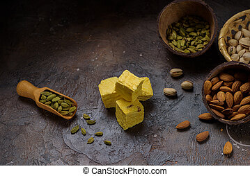 Cubes of dessert patisa, cardamom grains in wooden scoop, pistachios and almond on concrete kitchen surface with copy space.