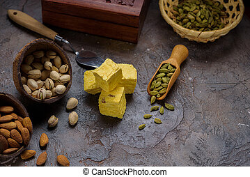 Cubes of dessert patisa, cardamom grains in wooden scoop, pistachios and almond on concrete kitchen worktop.