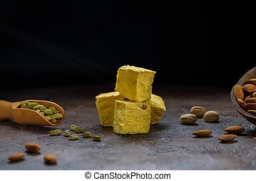 Cubes of dessert soan papdi, cardamom grains in wooden scoop, pistachios and almond on concrete kitchen surface with black copy space.