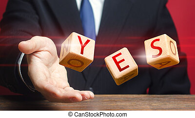 Cubes thrown by a man make up word YES. Agreement and acceptance, answer the question. Confirmation and approval. Important decision. Correct answer. Courage, irresistibility, zeal forwards, consent.