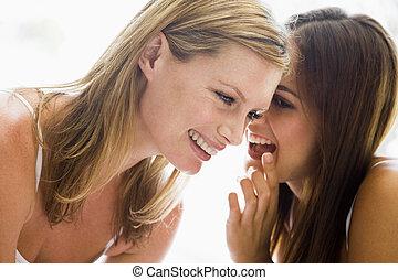 cuchicheo, sonriente, dos mujeres