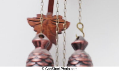 A close up view of the swinging pendulum on a Swiss cuckoo clock.