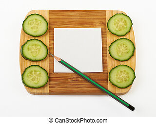 Cucumber and notepad on wooden board.