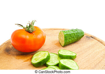 cucumber and tomato on wooden cutting board