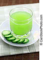 Cucumber juice next to cucumber slices