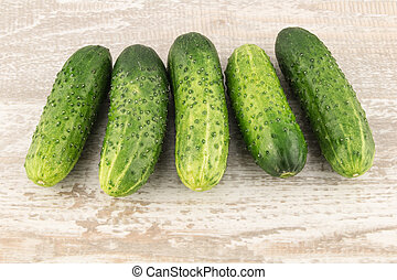 Cucumber on white wooden background close up.