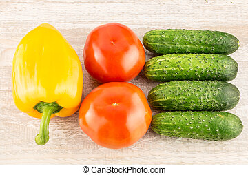 Cucumber, tomato, pepper and fennel on a white wooden background close up.