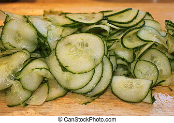 Cucumbers - A pile of cut sliced green cucumbers on a wooden...
