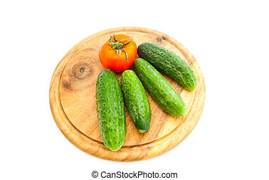 cucumbers and tomato on cutting board