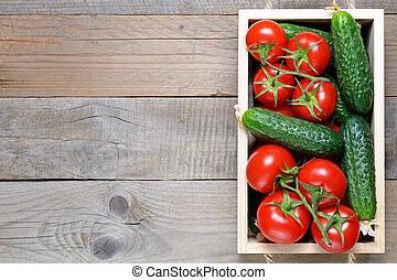 Cucumbers and tomatoes in box on wooden table