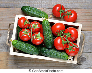 Cucumbers and tomatoes in wooden box top view