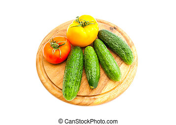 cucumbers and tomatoes on wooden cutting board