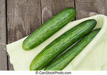 Cucumbers are lying on an old wooden background with napkin