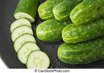 cucumbers and a cucumber cut in circles, washed and placed in a black ceramic plate isolated on white background