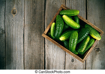Cucumbers in a box on wooden background.