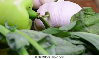 Cucumbers, onions, garlic and pepers in wicker basket on brown backround. Rotating vegetables. Closeup