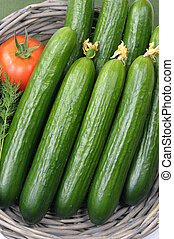 Smooth cucumbers in a basket with a tomato.