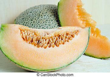 Cucumis melo or melon with half and seeds on wooden plate (Other names are cantelope, cantaloup, honeydew, Crenshaw, casaba, Persian melon, and Santa Claus or Christmas melon)