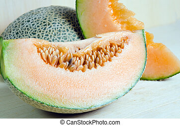 Sliced melon with seed on wooden board (Other names are cantelope, cantaloup, honeydew, Crenshaw, casaba, Persian melon, and Santa Claus or Christmas melon)