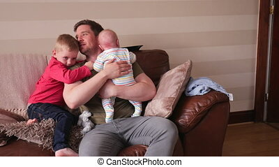 Cuddles with Dad - Father and his two sons sitting on the...