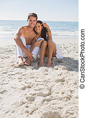 Cuddling couple smiling at camera sitting on sand at the...