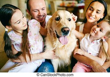 Cuddling dog - A young friendly family of four cuddling...