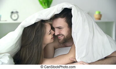Cuddling Under Sheets - Close up of sweet couple cuddling in...