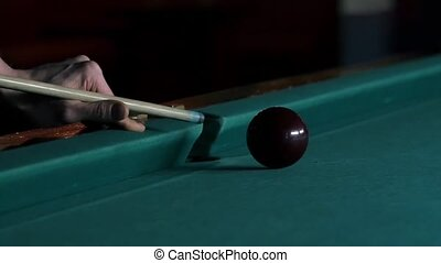 Cue hits white pool ball. Green billiard table. Close up. Slow motion