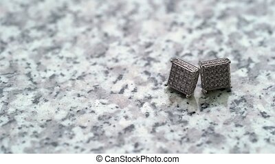 Cuff links on marble background at cloudy day