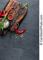 Culinary background with a space for a text. Flat lay composition of chili peppers, rosemary, spices and skewers for shish kebab on a black surface, top view