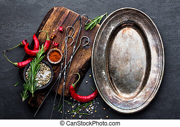 Culinary background with empty metal plate and space for a text. Flat lay composition of chili peppers, rosemary, spices and skewers for shish kebab on a black surface, top view