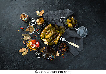 Culinary background with pickled cucumbers on a black background with space to copy.