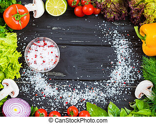 Culinary black wooden frame background with fresh vegetables, yellow paprika pepper, basil, cherry tomatoes, mushrooms, red onion, lime, lettuce. Food top view. Marine salt in middle