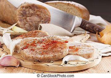 Culinary brawn. - Brawn piece and slices with garlic, onion,...