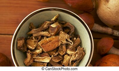 dried mushrooms in bowl on wooden background