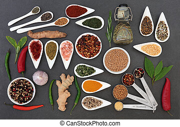 Culinary herb and spice selection with rosemary olive oil and measuring spoons on slate background.