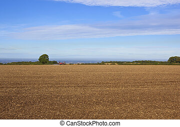 a red tractor with sprayer in a cultivated field on the yorkshire wolds england at harvest time under a blue sky