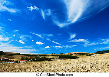 Cultivated land - Pale blue and white sky over cultivated...