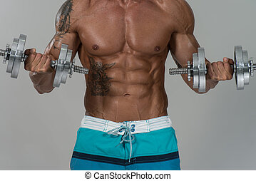 culturista, ejercitar, bíceps, con, dumbbells, en, gris,...