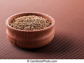 cumin in a wooden bowl on a brown background