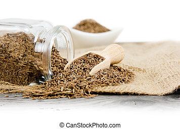 Cumin - Photo of glass spicebox full of cumin on burlap with...