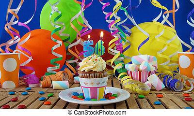 cumpleaños, cupcake, con, velas que queman, en, rústico, tabla de madera, con, plano de fondo, de, globos coloridos, tazas de plástico, y, golosinas, con, pared azul, en, el, plano de fondo