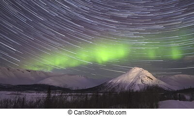 Cumulative Time Lapse of Night Starry Sky with Star Trails and Green Northern Lights in Snowy Mountains at Winter Night.