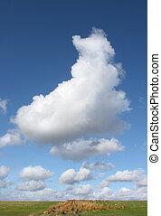 Cumulus Clouds - Cumulus clouds rising in a blue sky above a...