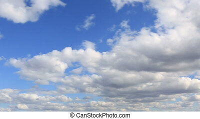 Cumulus clouds float across the blue sky. Timelapse View.