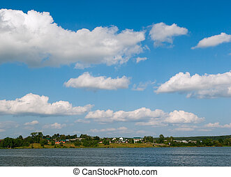 Cumulus Clouds over Lake - panoramic landscape. clouds over...