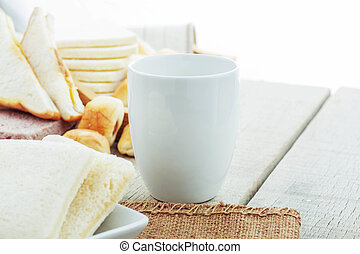 Cup and bread on table.