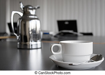 Reflective coffee pot next to an empty white cup. Laptop in the background.