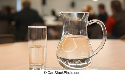 Cup and pitcher filled with water stand on table in conference hall