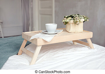 Cup and pot plant on bed tray